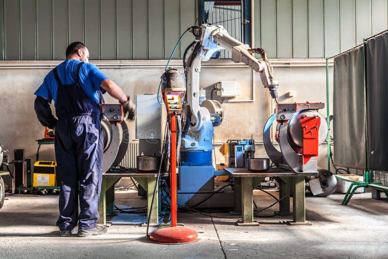 Mężczyzna i mechanicznego maszynowego pracy wpólnie inside przemysłowy budynek zdjęcie royalty free