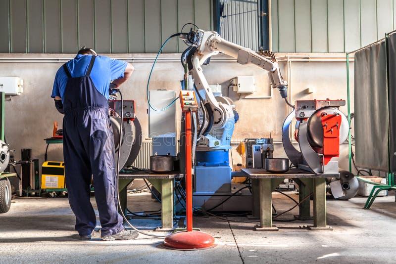 Mężczyzna i mechanicznego maszynowego pracy wpólnie inside przemysłowy budynek zdjęcia royalty free