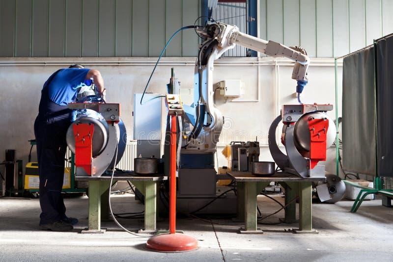 Mężczyzna i mechanicznego maszynowego pracy wpólnie inside przemysłowy budynek obrazy stock