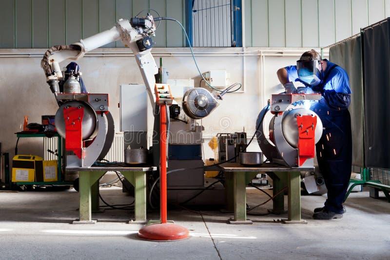 Mężczyzna i mechanicznego maszynowego pracy wpólnie inside przemysłowy budynek fotografia stock
