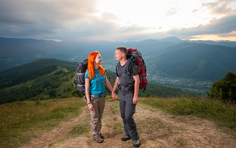 Mężczyzna i miedzianowłosa kobieta na drodze w górach obrazy stock