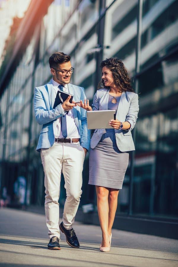 Mężczyzna i piękna kobieta jako partnery biznesowi używa cyfrową pastylkę plenerową fotografia royalty free