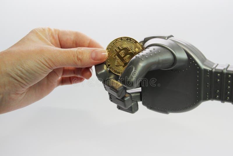 Mężczyzna i robot trzymamy jeden złocistą monetę - bitcoin zdjęcie royalty free