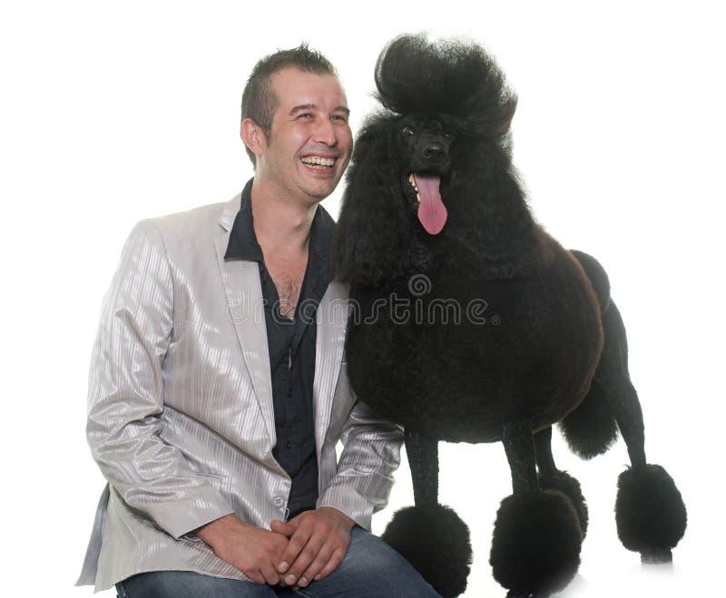 Mężczyzna i standardowy czarny pudel zdjęcia stock