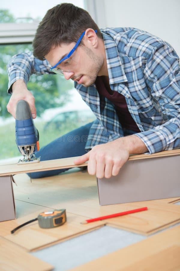 Mężczyzna instalujący nowe laminowane drewniane podłoże obrazy stock