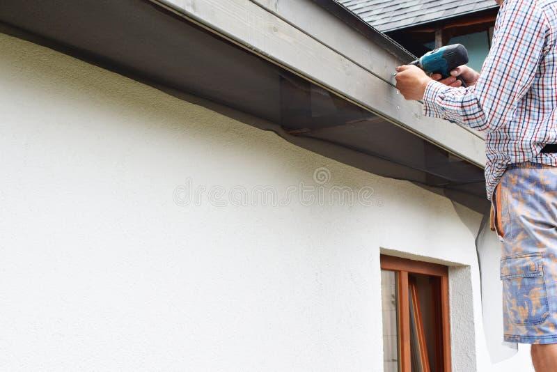 Mężczyzna instaluje dachowych okapy fotografia stock