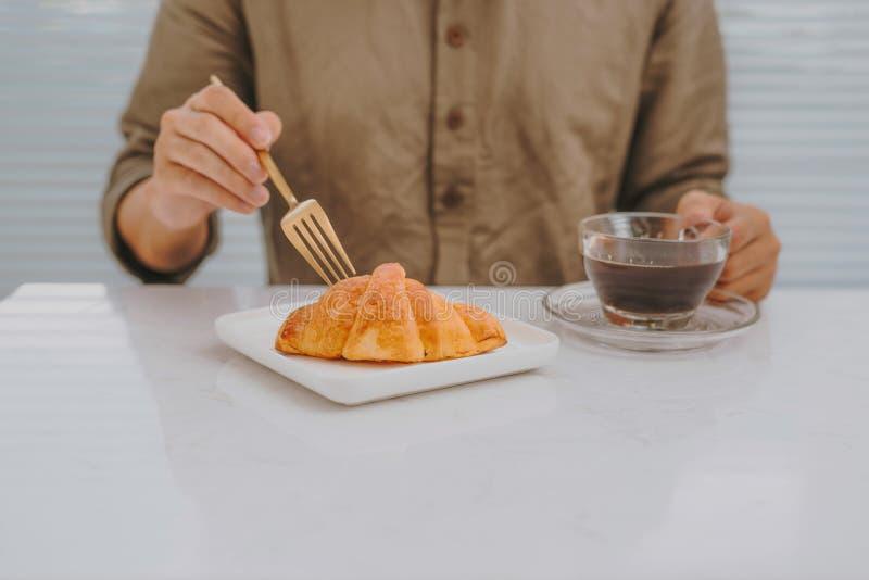 Mężczyzna je świeżego croissant piec na sobota rano, Francuski croissant na stole przy piekarnia sklepem, Croissant piec na taler fotografia royalty free