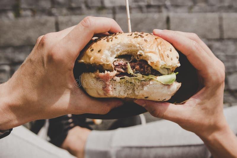 Mężczyzna je świeżego smakowitego piec na grillu hamburger Odgórny widok zdjęcia royalty free