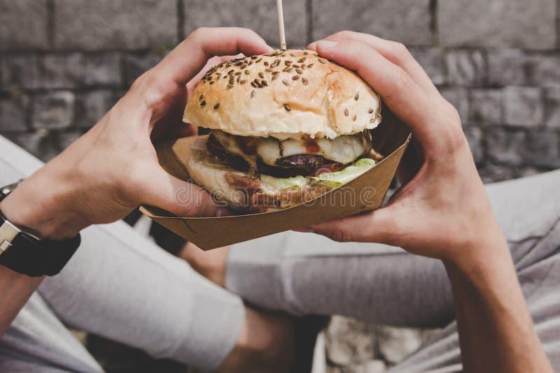 Mężczyzna je świeżego smakowitego piec na grillu hamburger Odgórny widok fotografia stock