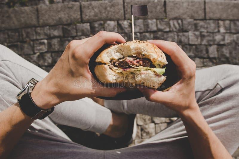 Mężczyzna je świeżego smakowitego piec na grillu hamburger Odgórny widok zdjęcia stock