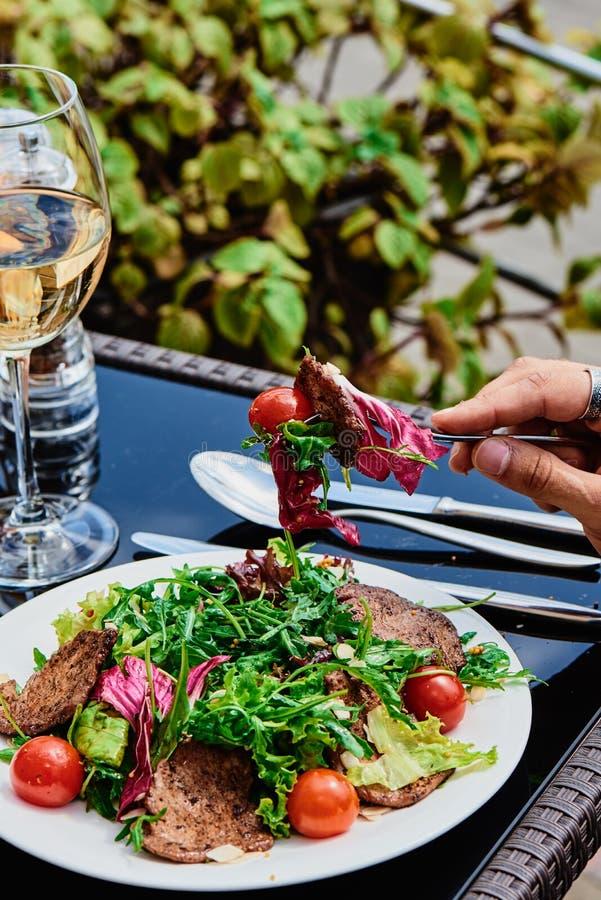 Mężczyzna je świeżej sałatki z warzywami i ciepłym mięsem w białym talerzu na ciemnego szkła stole na lato tarasie zdjęcia royalty free