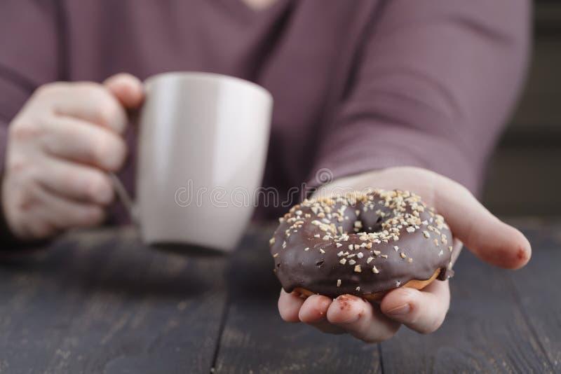 Mężczyzna je czekoladowego pączek zdjęcia stock