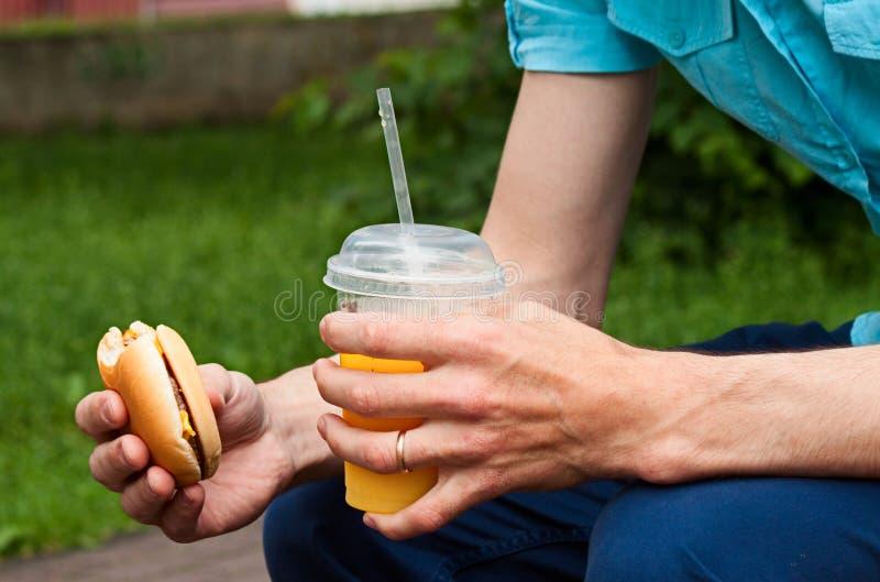 Mężczyzna je fast food na ulicie obrazy royalty free