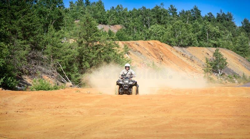 Mężczyzna jedzie ATV kwadrat w piaskowatym terenie z wysoką prędkością zdjęcia royalty free