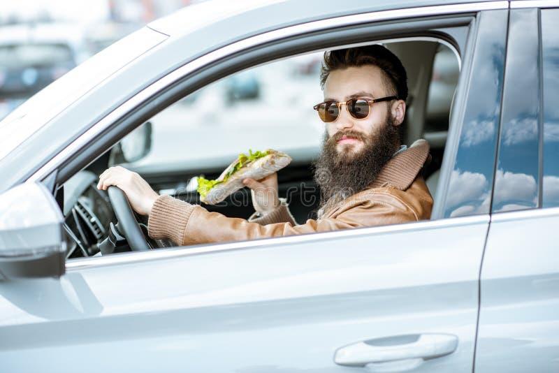 Mężczyzna jedzie samochód z kanapką obrazy royalty free