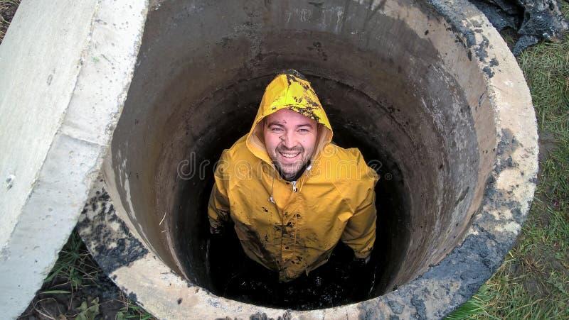 Mężczyzna jest inside kanalizacyjnym jamą, kanalizacyjne pracy, pracuje blisko domu fotografia stock
