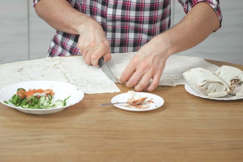 Mężczyzna jest kulinarnym shawarma na kuchennym stole w domu Pita, warzywa i zielona cebula z, kumberlandem i majonezem zakończen zdjęcie stock