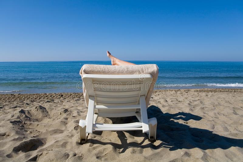 Mężczyzna jest odpoczynkowy na deckchair morzem obrazy royalty free