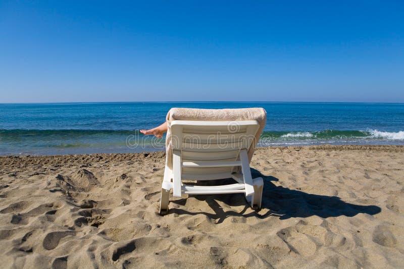 Mężczyzna jest odpoczynkowy na deckchair morzem obraz stock