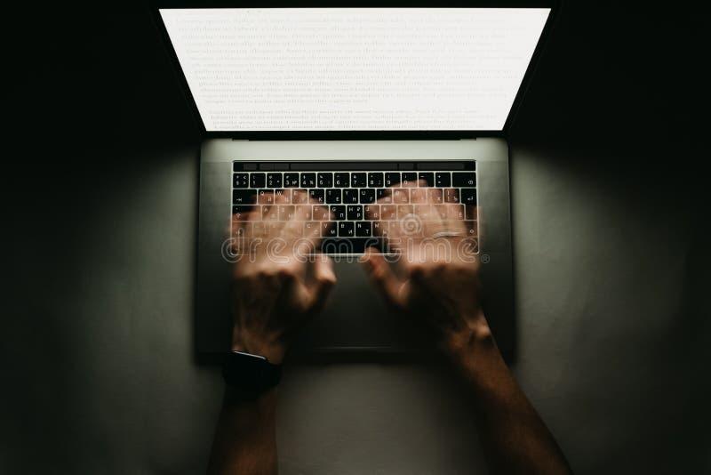 Mężczyzna jest pracującym pisać na maszynie use laptopem przy zmrokiem fotografia royalty free