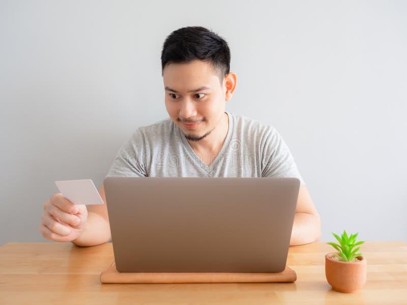 Mężczyzna jest szczęśliwy używać kartę kredytową dla cyfrowej zapłaty zdjęcie stock