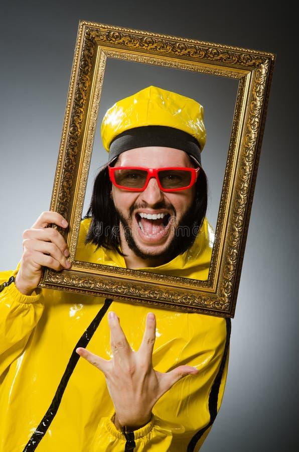Mężczyzna jest ubranym żółtego kostium z obrazek ramą fotografia royalty free