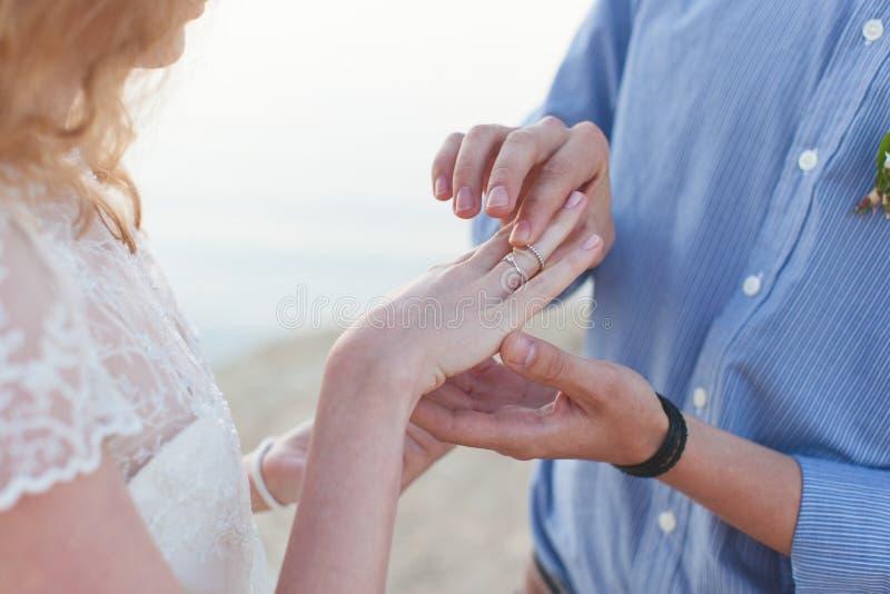 Mężczyzna jest ubranym obrączkę ślubną na palcu dziewczyna obraz stock