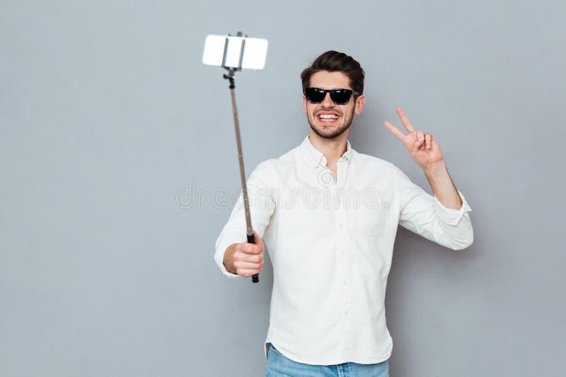 Mężczyzna jest ubranym okulary przeciwsłonecznych bierze fotografie z smartphone i selfie kijem zdjęcie royalty free