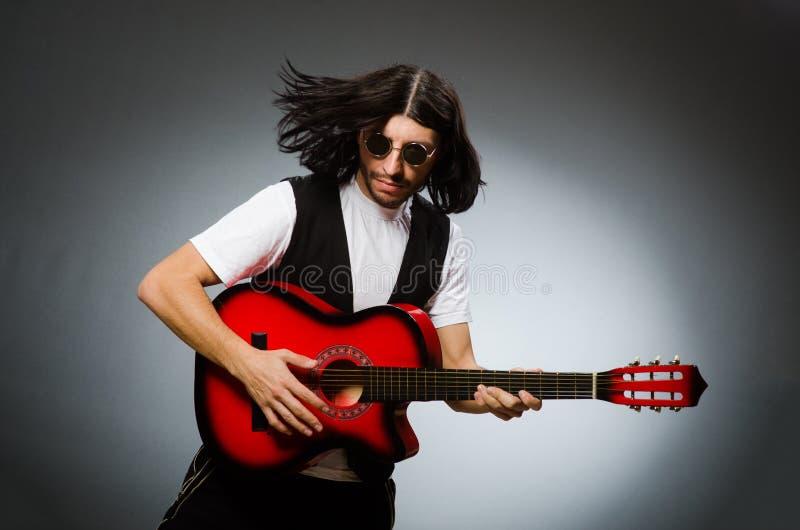 Mężczyzna jest ubranym okulary przeciwsłonecznych i bawić się gitarę obraz stock