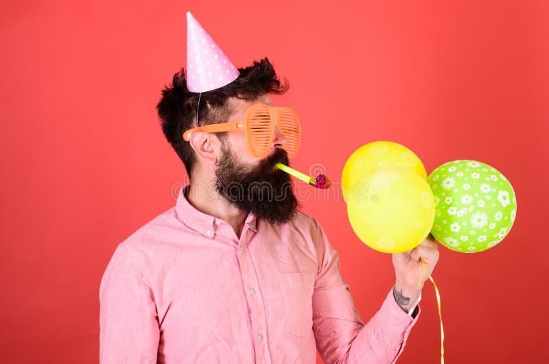 Mężczyzna jest ubranym różową koszula i przyjęcia nakrętkę na czerwonym tle z naszywaną brodą Brodaty mężczyzna dmuchania przyjęc zdjęcie stock