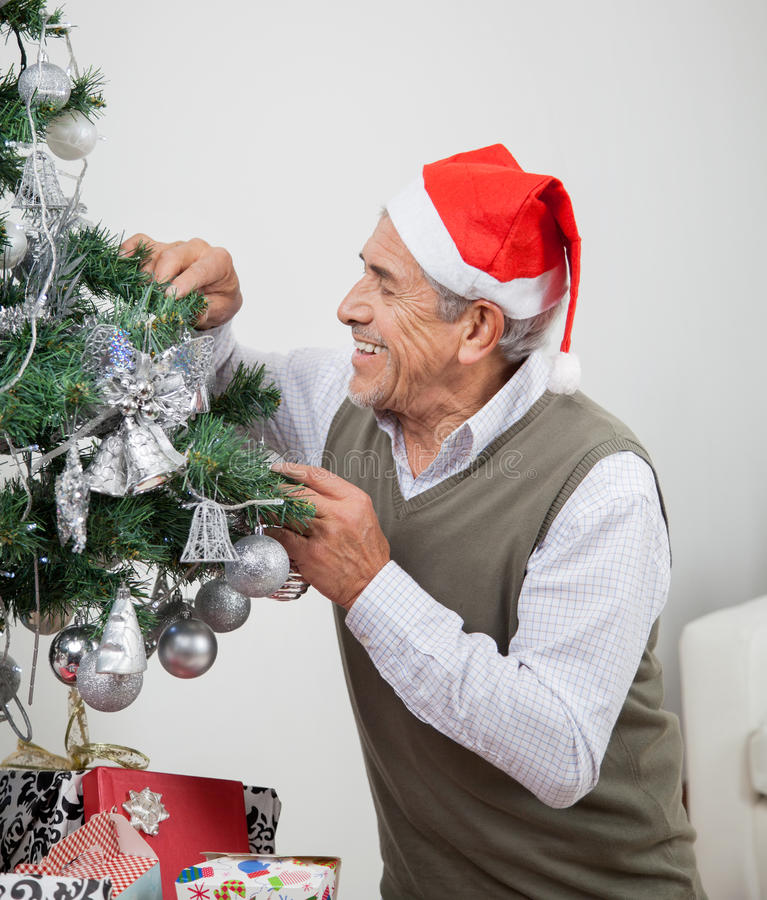 Mężczyzna Jest ubranym Santa Kapeluszowej Dekoruje choinki obrazy royalty free