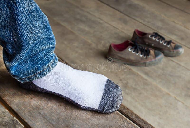 Mężczyzna jest ubranym skarpety stawiają stopę na drewnianym foor obrazy stock