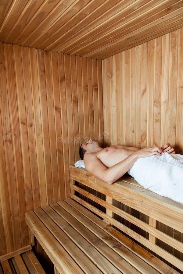 Mężczyzna kłaść wśrodku sauna zdjęcia royalty free