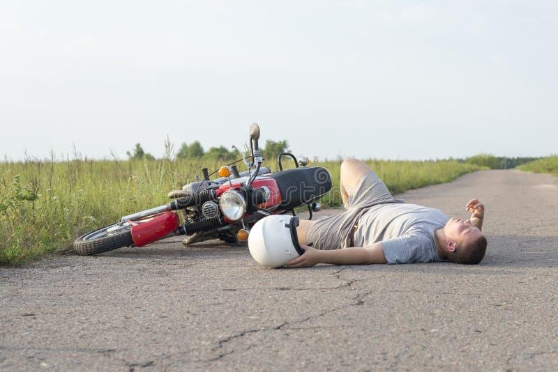 Mężczyzna kłama na asfalcie blisko motocyklu temat wypadki drogowi zdjęcie royalty free