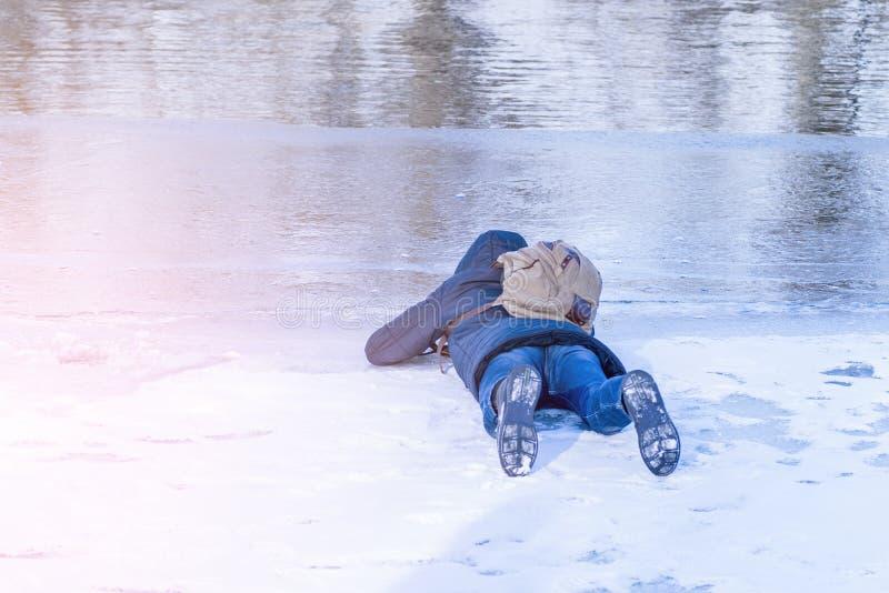 Mężczyzna kłama na lodzie w zimie, mężczyzny kłamstwach na lodzie zimy rzeka i spojrzeniach, przez lodu na rozjaśniam od śniegu obraz royalty free