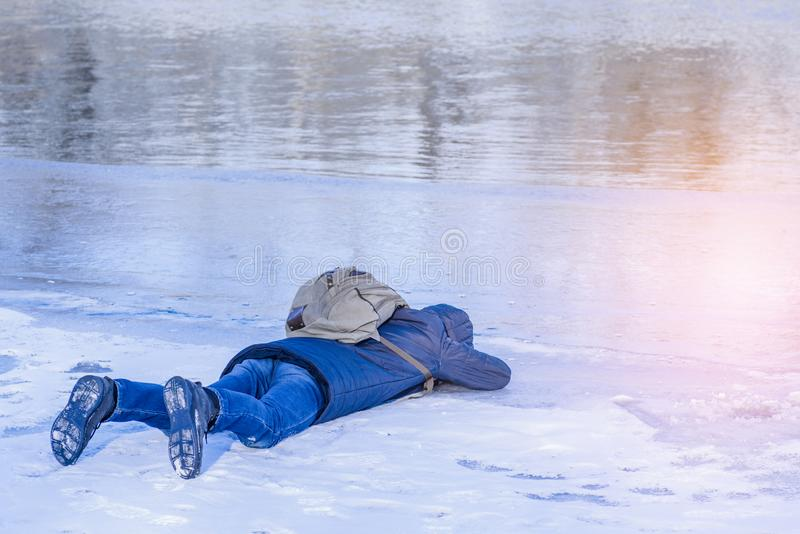Mężczyzna kłama na lodzie w zimie, mężczyzny kłamstwach na lodzie zimy rzeka i spojrzeniach, przez lodu na rozjaśniam od śniegu zdjęcia stock