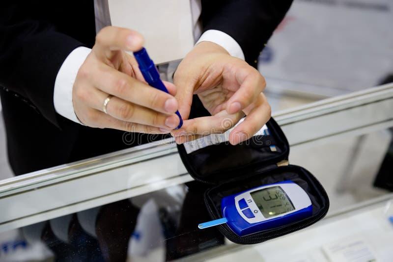 Mężczyzna kłuje palec dla pomiarowej glikozy równej w jego krwionośnej kropli używać cyfrowego glucometer fotografia royalty free