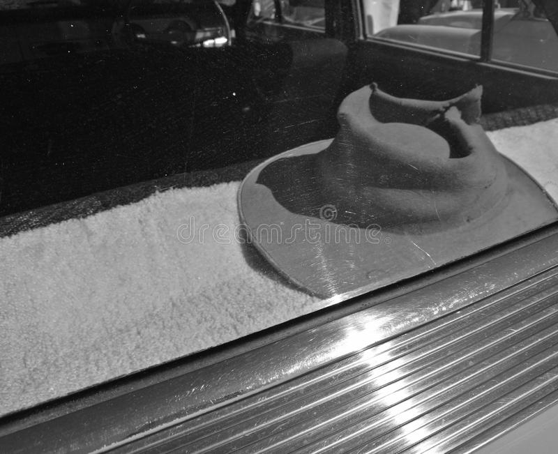 Mężczyzna kapeluszowej lewicy inside samochodowa przednia szyba w czarny i biały obraz royalty free