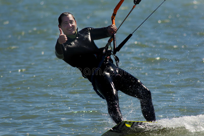 Mężczyzna kiting na wodzie daje aprobatom zdjęcia royalty free
