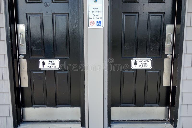 Mężczyzna kobiet łazienki czarni drzwi z mężczyzna pchnięciem Zadawalają znaka na drzwi fotografia stock