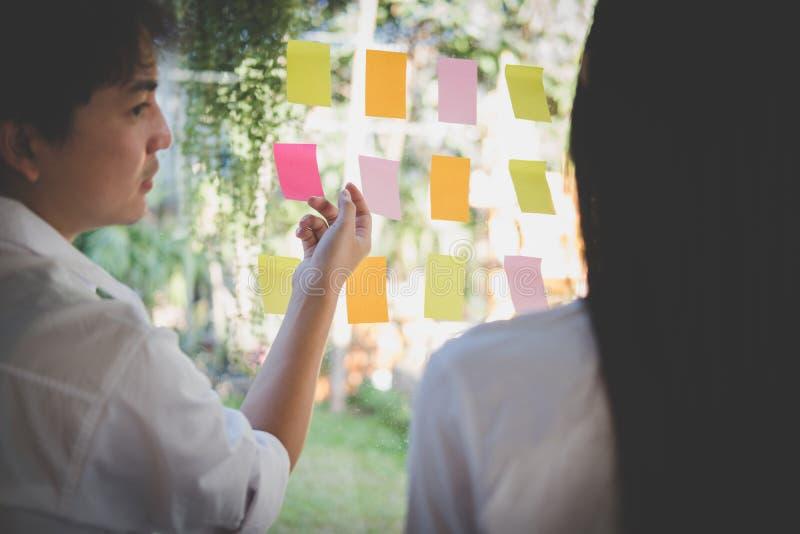 Mężczyzna & kobieta dyskutuje kreatywnie pomysł z adhezyjnymi notatkami na glas obrazy stock