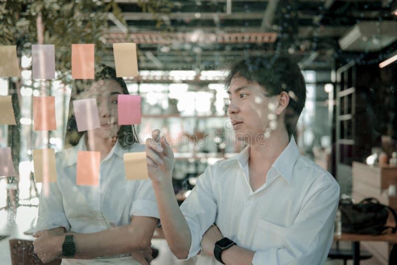 Mężczyzna & kobieta dyskutuje kreatywnie pomysł z adhezyjnymi notatkami na glas fotografia royalty free