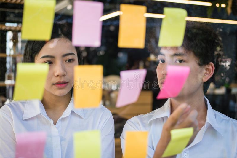 Mężczyzna & kobieta dyskutuje kreatywnie pomysł z adhezyjnymi notatkami na glas zdjęcie royalty free