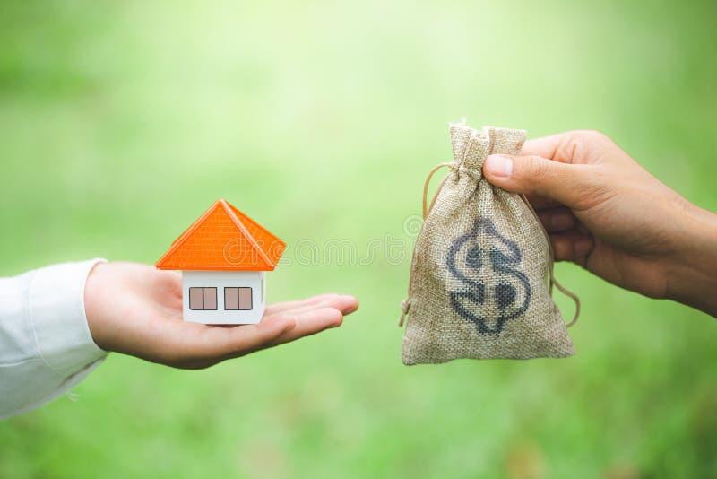 Mężczyzna, kobiety ręka, kupienie i sprzedawanie trzyma pieniądze torbę i wzorcowego domu Naturalnego zielonego tło, dom, pożyczk obraz royalty free