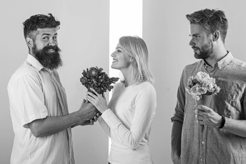 Mężczyzna konkurenci z bukietów kwiatów próbą podbijają dziewczyny Dziewczyny ono uśmiecha się robić jej wybór pojęcia łamany ser obraz royalty free