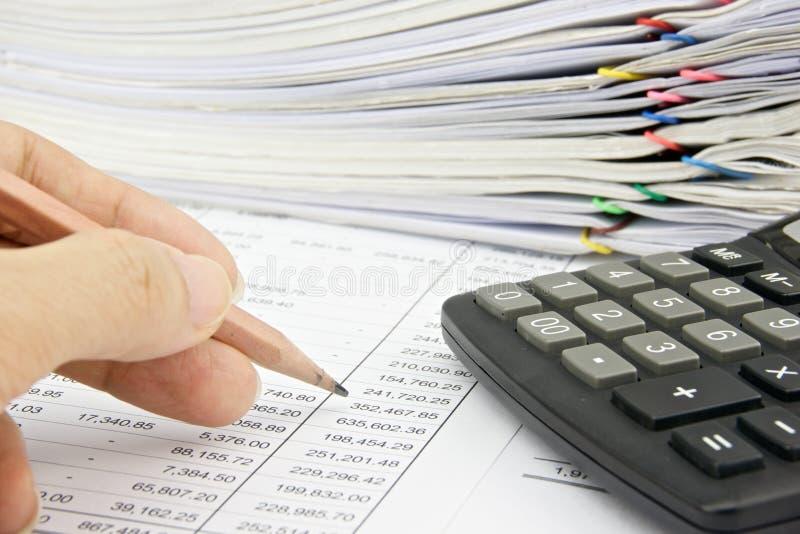Mężczyzna kontroluje konto z ołówkiem i kalkulatorem zdjęcie royalty free