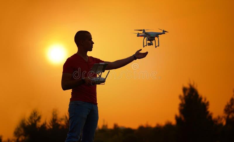 Mężczyzna kontroluje quadrocopter Ciepła zmierzch fotografia obraz stock