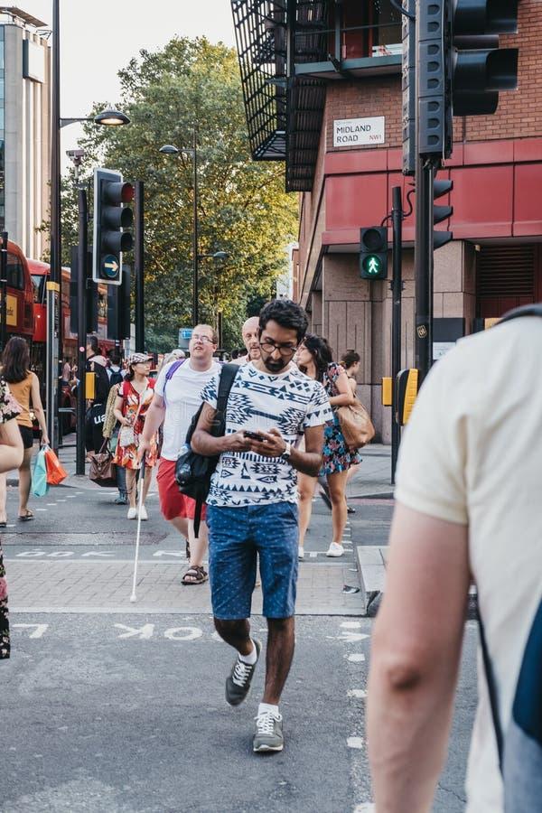Mężczyzna krzyżuje drogę w kierunku królewiątka ` s krzyża staci, Londyn, UK fotografia royalty free