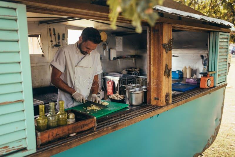 Mężczyzna kucharstwo w mobilnej jedzenie ciężarówce obrazy royalty free