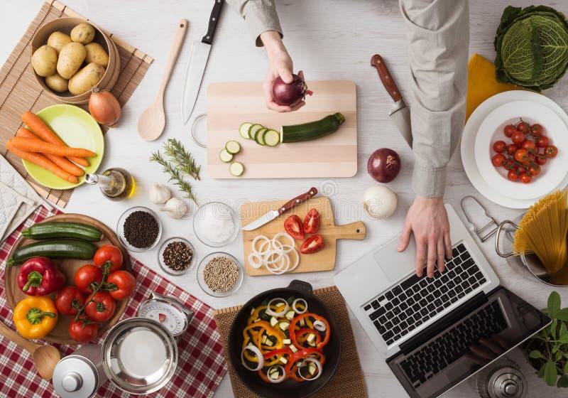 Mężczyzna kucharstwo z laptopem zdjęcia stock